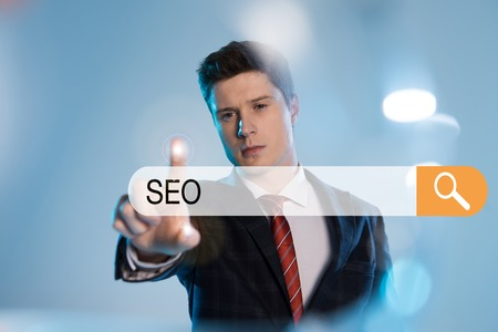 confident businessman in suit pointing with finger at search bar with seo letters in front on blue background