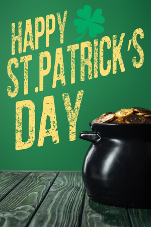 golden coins in pot  with happy st patricks day lettering on green background