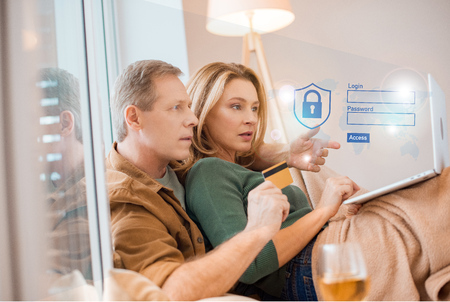 couple looking at laptop screen together while husband holding credit card, smart home concept