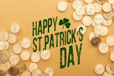 top view of golden coins near happy st patricks day lettering on orange background