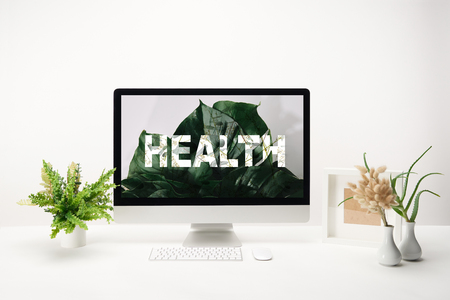 computer with health lettering and tropical green leaves on monitor on desk on white background