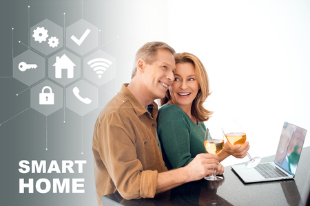 happy couple holding glasses of white wine while standing by table with laptop, smart home concept