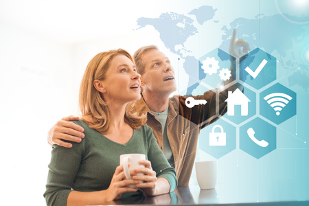 selective focus of amused couple with coffee cups, smart home concept