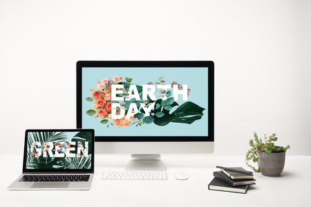 computer with earth day lettering on monitor and laptop with green lettering on screen on desk on white background