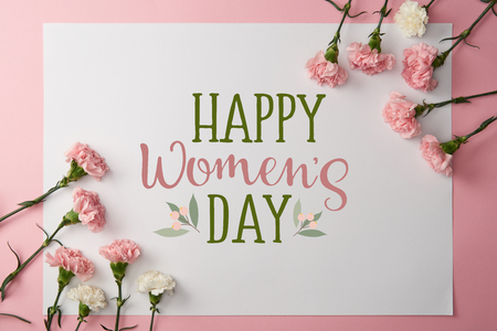 top view of pink and white carnation flowers and greeting card with happy womens day lettering on pink background Zdjęcie Seryjne