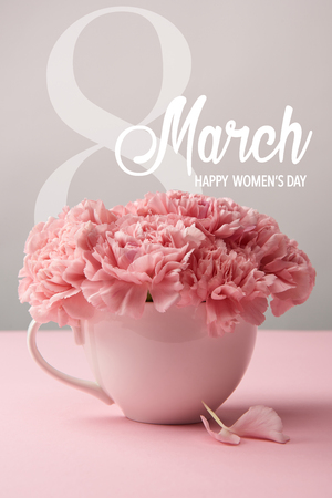 pink carnation flowers in cup on grey background with 8 march lettering