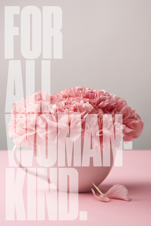 pink carnation flowers in cup on grey background with for all woman kind lettering