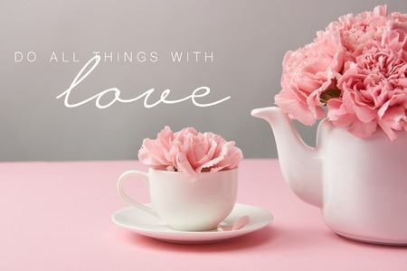 pink carnation flowers in cup and teapot on grey background with do all things with love lettering