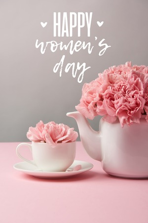 pink carnation flowers in cup and teapot on grey background with happy womens day lettering