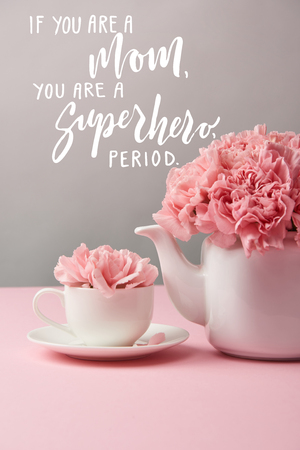 pink carnation flowers in cup and teapot on grey background with if you are a mom, you are a superhero, period lettering