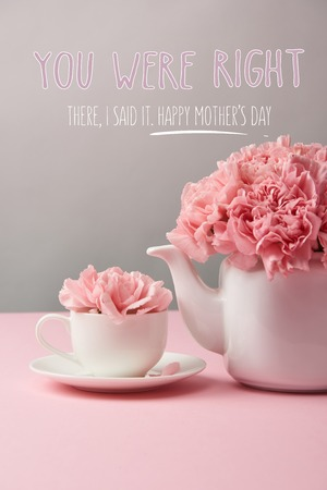 pink carnation flowers in cup and teapot on grey background with happy mothers day lettering