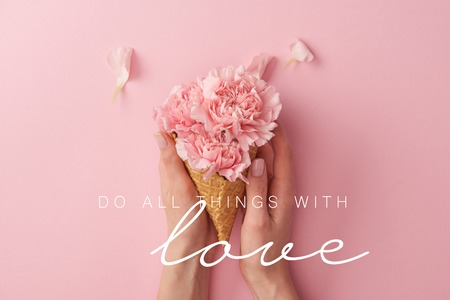 cropped view of woman holding pink carnation flowers in hands with do all things with love illustration Фото со стока