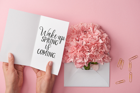 cropped view of woman holding greeting card with wake up, spring is coming lettering near carnation flowers in envelope on pink background