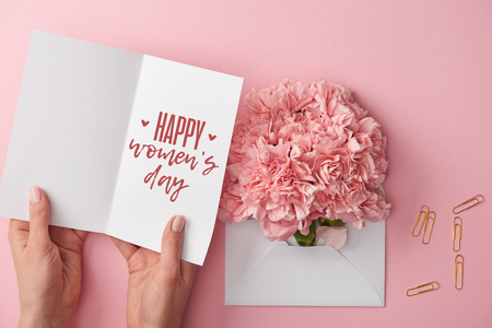 cropped view of woman holding greeting card with happy womens day lettering near carnation flowers in envelope on pink background Stock Photo