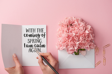 cropped view of woman holding spring greeting card and pen near carnation flowers in envelope on pink background Stock Photo