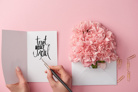 cropped view of woman holding greeting card with trust your soul lettering and pen near carnation flowers in envelope on pink background Banco de Imagens