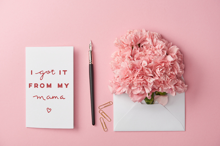 top view of mothers day greeting card and envelope with carnations on pink background Stock Photo