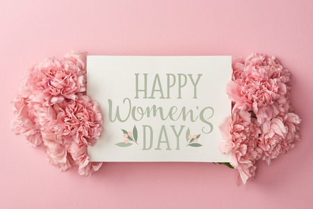 top view of greeting card with happy womens day lettering and pink carnations on pink background Фото со стока - 119970250