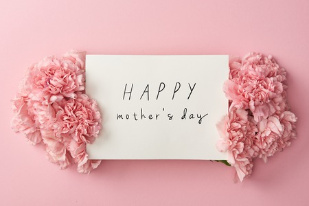 top view of greeting card with happy mothers day lettering and pink carnations on pink background