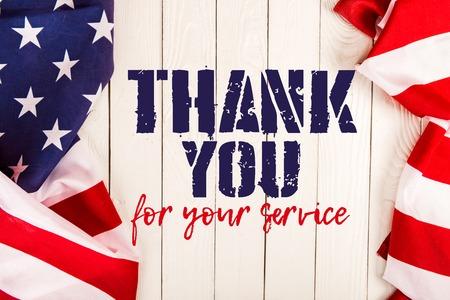 vista dall'alto delle bandiere americane e grazie per il vostro servizio scritte su una superficie di legno bianco