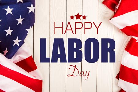 vista dall'alto delle bandiere americane e della scritta Happy Labor Day su superficie in legno bianco white