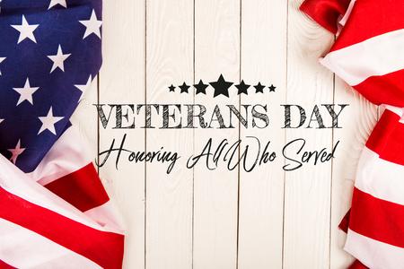 Draufsicht auf amerikanische Flaggen und Veteranentag-Schriftzug auf weißer Holzoberfläche