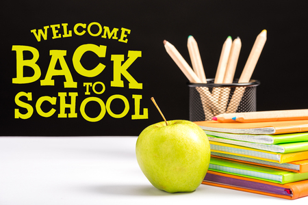 fresh apple, notebooks and color pencils on table with welcome back to school  lettering on black Banco de Imagens
