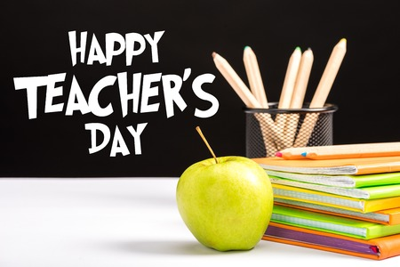 fresh apple, notebooks and color pencils on table with happy teachers day  lettering on black Stock Photo