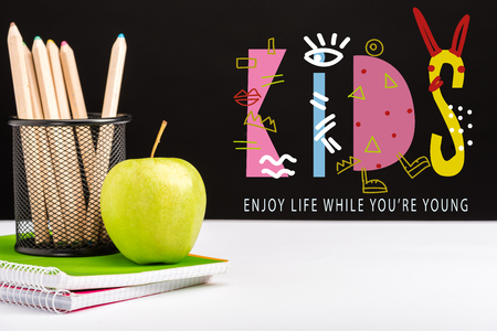 green apple, notebooks and color pencils on table with enjoy life while you are young and kids lettering on black Foto de archivo - 119438494