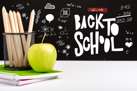 fresh apple, notebooks and color pencils on table with welcome back to school  lettering and icons on black Stockfoto