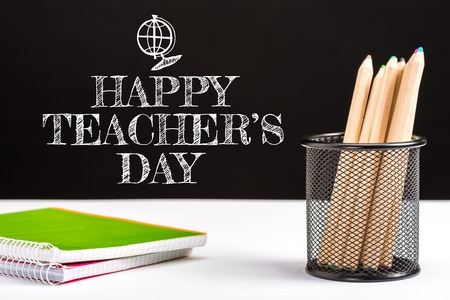 notebooks and color pencils on table with white happy teachers day lettering on black Stock Photo