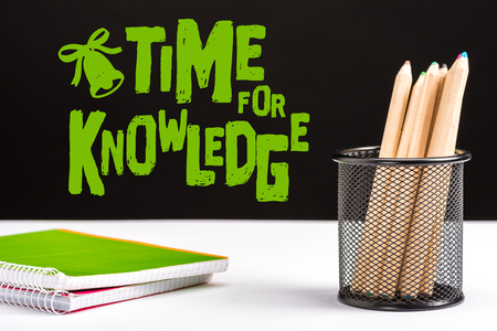 notebooks and color pencils on table with green time for knowledge lettering and bell sign on black Stock Photo