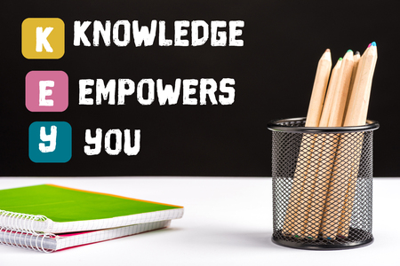 notebooks and color pencils on table with key and knowledge empowers you lettering on black Stok Fotoğraf