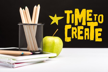 fresh apple, notebooks and color pencils on table with time to create lettering and star on black