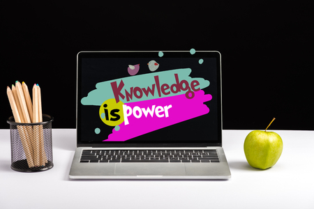 fresh green apple, color pencils and laptop on table with knowledge is power lettering on screen isolated on black