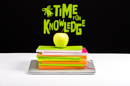 closed laptop, pile of notebooks with green apple on top with time for knowledge lettering on black