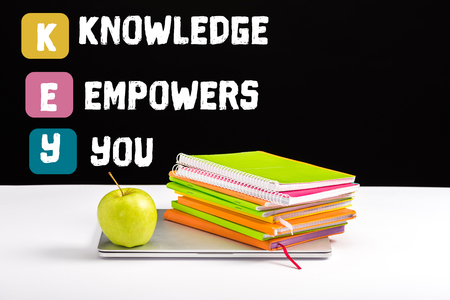 closed laptop, green apple, notebooks and color pencils on desk with knowledge empowers you lettering on black Foto de archivo - 119970300