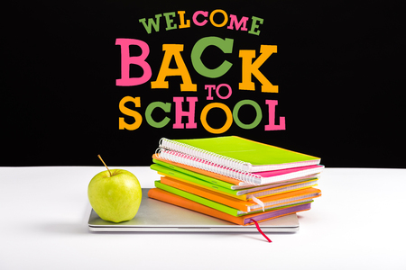 closed laptop, green apple, notebooks and color pencils on desk with welcome back to school lettering on black