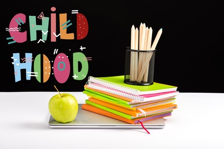 closed laptop, green apple, notebooks and color pencils on desk with childhood lettering on black