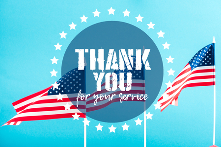 american flags with thank you for your service lettering on blue