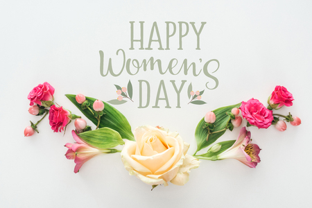 top view of roses and alstroemeria flowers composition on white background with happy womens day lettering