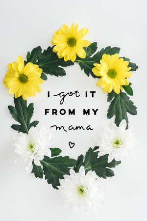 top view of wreath with white and yellow daisies and green leaves on white background with i got it from my mama lettering