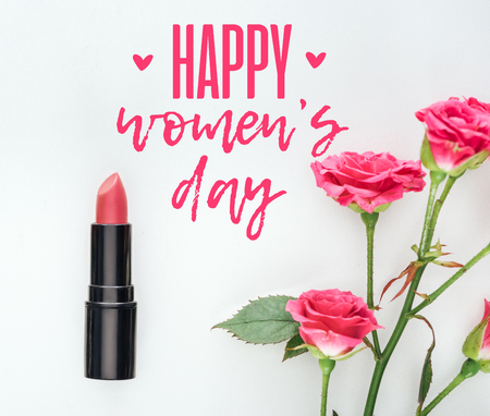 top view of lipstick and pink roses on white background with happy womens day lettering Stock Photo