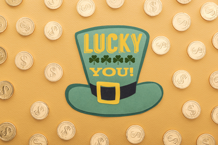 top view of golden coins with dollar signs near green paper hat with lucky you lettering on orange background
