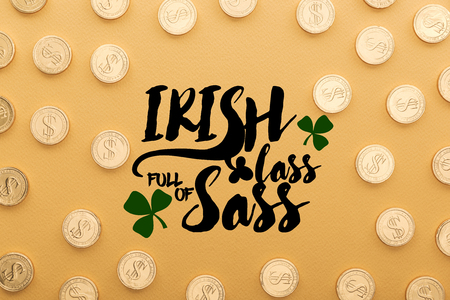 top view of shiny coins with dollar signs near irish lass full of sass lettering on orange background