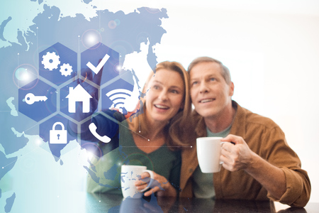 selective focus of amused happy couple holding coffee cups, smart home concept