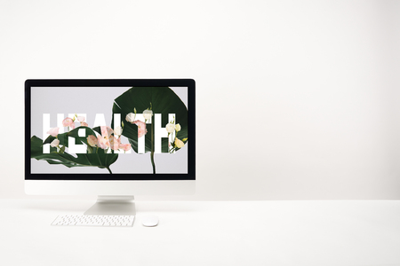 computer with health lettering and green monstera leaves on monitor on white background Stock Photo