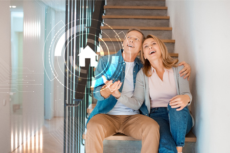excited couple sitting on stairs at new home, smart home concept 스톡 콘텐츠