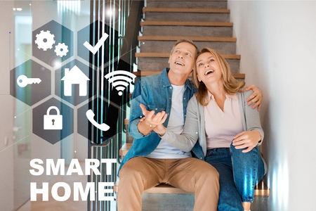 happy husband and wife sitting on stairs at new home, smart home concept Zdjęcie Seryjne - 119438544