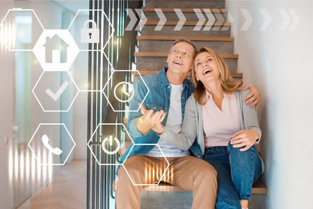 inspired smiling couple sitting on stairs at new home, smart home concept